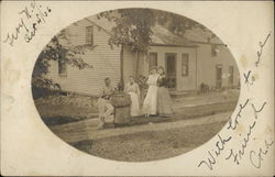 Family Posing In Front of Home